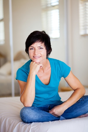 thirties: modern middle aged woman sitting on bed relaxing  Stock Photo