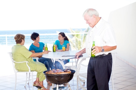 grandpa doing barbeque for the family on balcony  photo