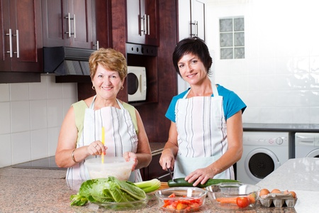 holiday cooking: happy middle aged woman cooking with senior mother in kitchen