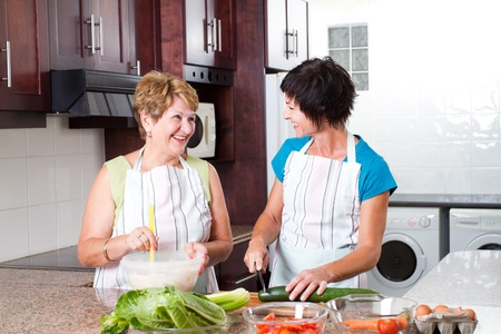 happy senior mother and middle aged daughter cooking in kitchen photo