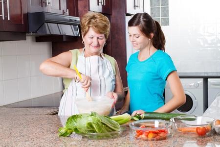 mujeres cocinando: nieta de la abuela viendo cocinar en la cocina Foto de archivo