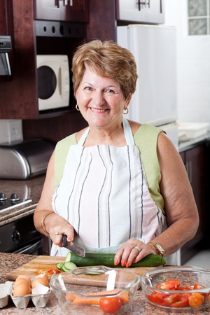 woman cooking: happy senior woman cooking in kitchen Stock Photo