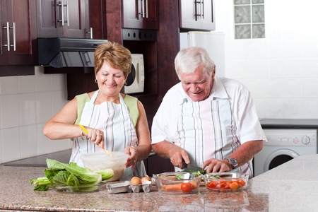 elderly couple cooking in home kitchen photo