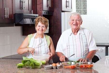 happy senior couple cooking in home kitchen photo