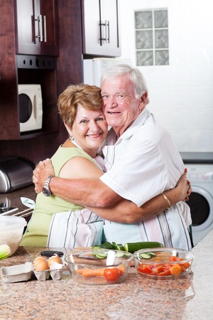 happy loving senior couple hugging in kitchen photo
