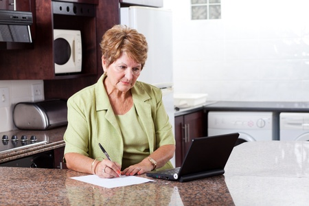 riches adult: senior woman doing home finance and looks worried