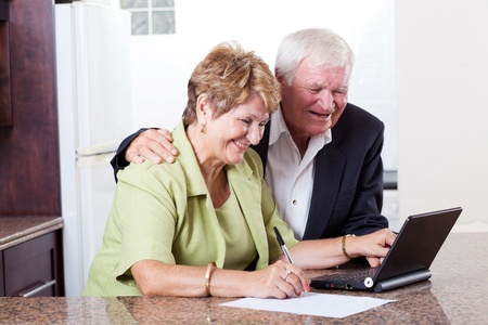 donna ricca: felice coppia senior con internet banking controllo conto in banca