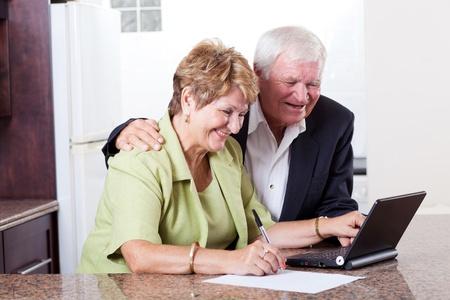 rich man: feliz pareja senior de banca por Internet con control de saldo en el banco Foto de archivo