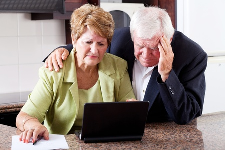 worry: unhappy senior couple worrying about expenses at home