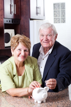 retirement savings: retirement savings concept: senior couple putting coins in piggybank