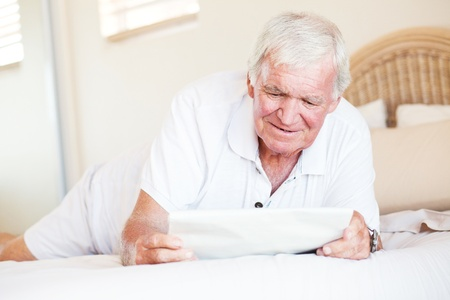 senior man lying on bed and reading newspaper Stock Photo - 12728255