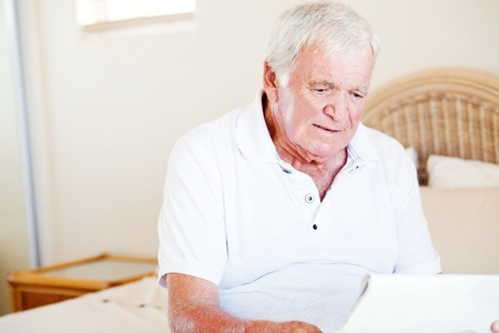 senior man sitting on bed and reading newspaper photo