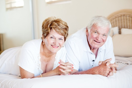 70s adult: happy senior couple lying on bed Stock Photo