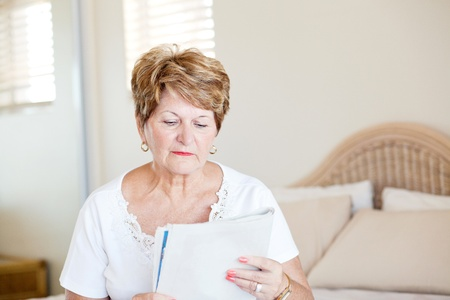 senior woman sitting on bed and reading newspaper photo