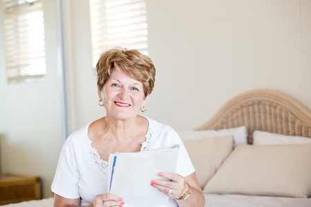 happy senior woman sitting on bed and reading newspaper photo