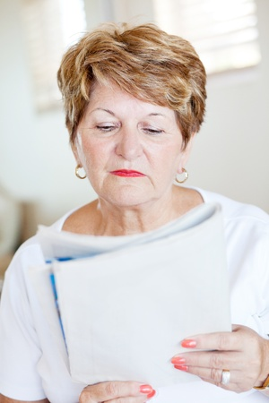 elderly woman reading newspaper photo