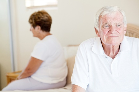 worry: unhappy senior couple sitting on bed