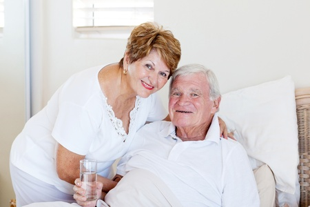 caring senior wife taking care of ill husband photo