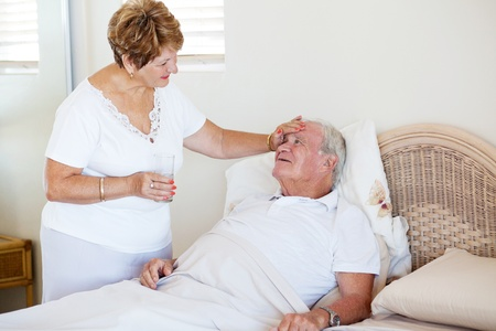 loving senior wife comforting ill husband photo