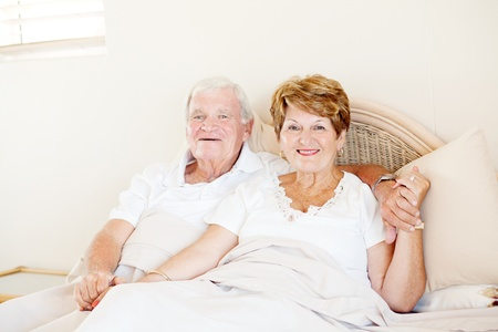happy senior couple holding hands in bed photo