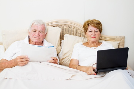 senior couple reading in bed before sleep photo