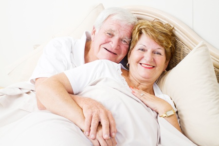 happy senior couple hugging in bed photo