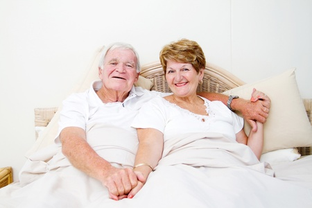 happy senior couple in bed relaxing photo