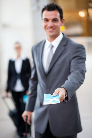 young businessman handing over air ticket, focus on ticket photo