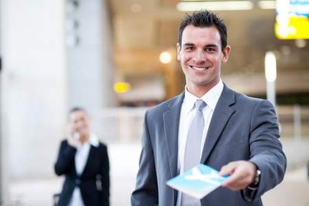 corporate airplane: businessman handing over air ticket in airport check in counter,