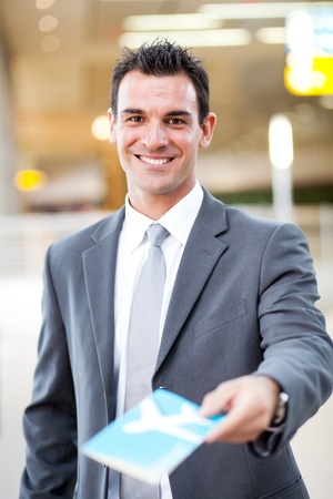 airport check in counter: smiling handsome businessman handing over air ticket at airport check in counter Stock Photo