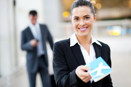 attractive businesswoman handing over air ticket at airport check in counter photo