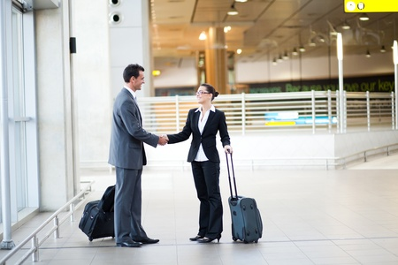 airport people: young businessman and businesswoman meeting at airport