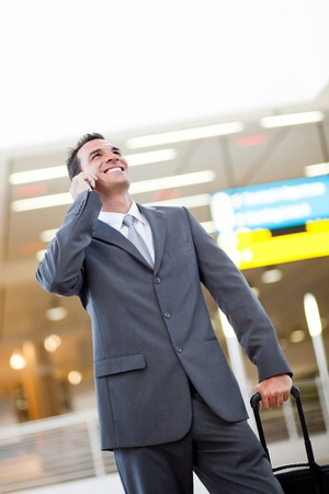 young businessman talking on cellphone at airport photo