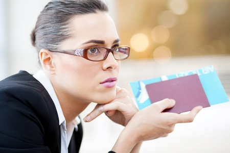 corporate travel: closeup of young businesswoman waiting for her flight in airport