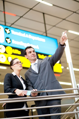 business travellers pointing at flight information board Stock Photo - 12897849