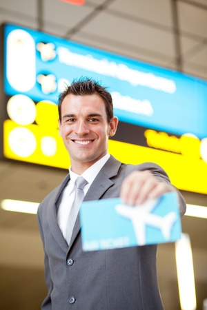 happy young businessman presenting air ticket  photo