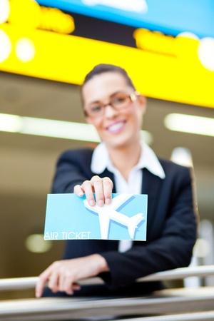young businesswoman presenting air ticket at airport, focus on foreground  photo