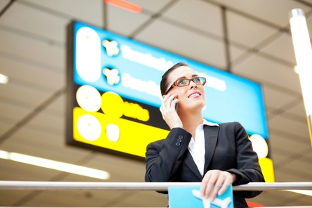 attractive young businesswoman talking on cell phone at airport at airport photo