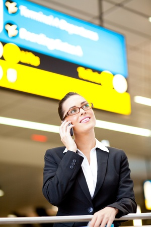 business traveller: pretty young businesswoman talking on cell phone at airport