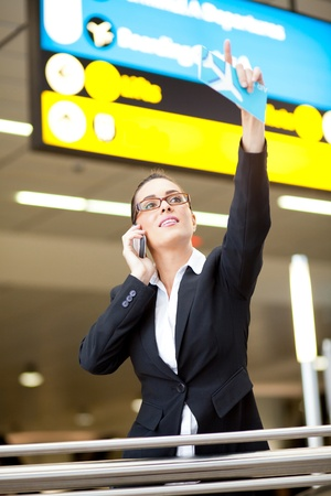 young businesswoman waving to someone while talking on cell phone at airport photo