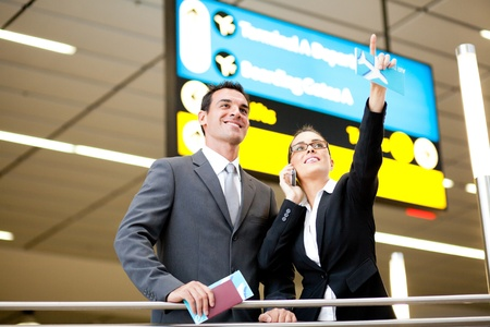 two business travellers checking boarding information at airport photo