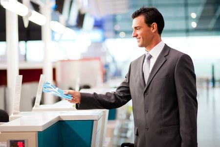 gente aeropuerto: apuesto hombre de negocios la entrega de billetes de avión en el mostrador de las aerolíneas