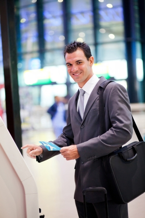 business trip: businessman using self help check in machine at airport Stock Photo