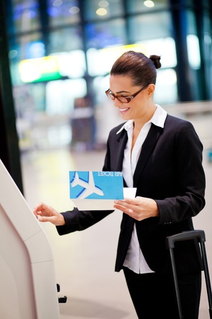 boarding: happy businesswoman using self help check in machine at airport