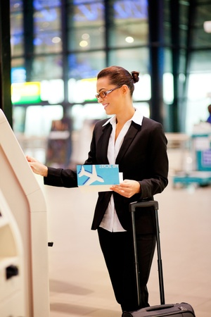 check in: businesswoman using self help check in machine in airport