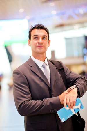 jetsetter: handsome businessman checking flight departure time at airport