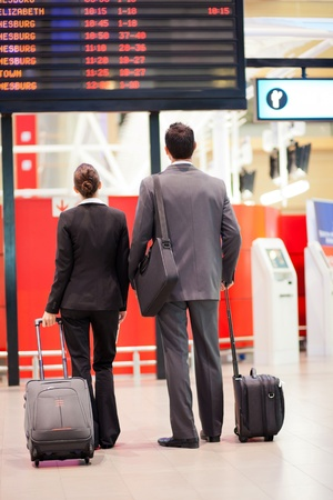 two business travellers looking at airport information board photo
