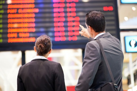 departure board: businessman and businesswoman checking flight information at airport Stock Photo