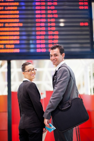 jetsetter: young businesswoman and businessman in front of airport information board