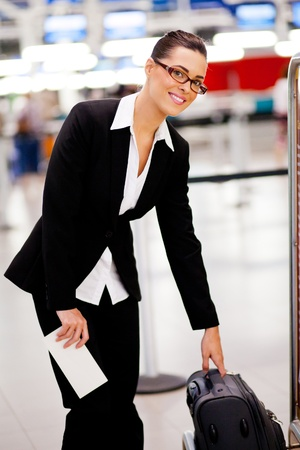 jetsetter: Businesswoman checking size of her carry-on luggage at airport Stock Photo
